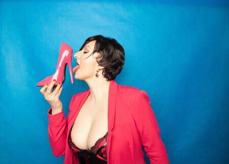 Más el tamaño de las mujeres morenas de pelo corto ama los zapatos de tacones altos de charol rosa y lo sostiene con un placer emocionante sobre fondo azul