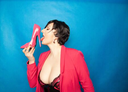 Plus size short hair brunette Women loves pink patent leather high heels shoes and holds it with exciting pleasure on blue background