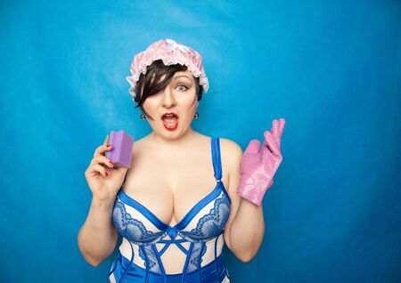 adorable happy plus size short hair woman in blue white lingerie with a rubber glove and a sponge for washing dishes on a solid background in Studio