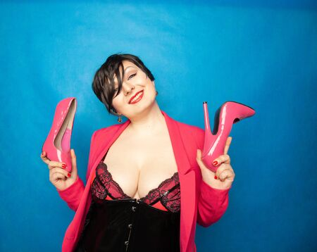 Plus size short hair brunette sexy Women loves pink patent leather high heels shoes and holds it with exciting pleasure on blue background