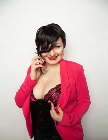 cute plus size girl with short black hair stands in a sexy bodice and pink business jacket with a smartphone in her hands Banco de Imagens