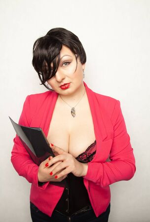 cute plus size girl with short black hair stands in a sexy bodice and pink business jacket with an office folder in her hands Banco de Imagens