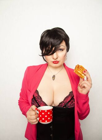 plus size girl with short black hair stands with a Cup of drink in her hands and an unhealthy snack on white background in the Studio Banco de Imagens