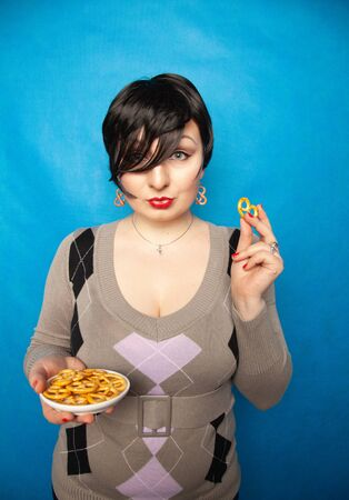 charming plus size girl in a sweater stands with a plate of salted pretzels and enjoys a snack on a blue background in the Studio