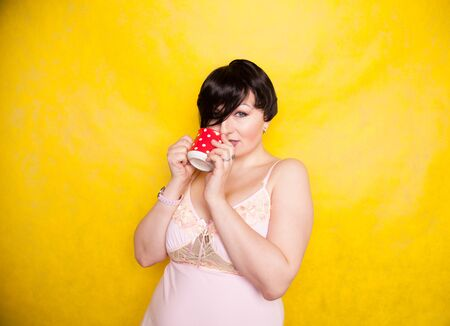 Plus sized woman wearing pink dress holding a red polka dot ceramic coffee or tea cup on a bright yellow background