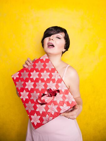 happy Female holding in hands big gift with ribbon. Adult girl with red present on yellow studio background. Stock Photo