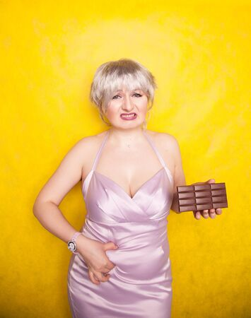 Womans fingers measuring her belly fat while she holding a chocolate bar on yellow solid studio background.