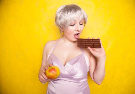 sweet joyous curvaceous girl with a short haircut stands in a delicate evening silk dress and compares bad and good food, deciding what health she wants for herself Banco de Imagens