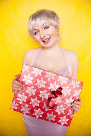 sweet joyous curvaceous girl with a short haircut and plus size body stands in a delicate evening lilac silk dress and holds a large bright red box with a gift for the holiday Stock Photo