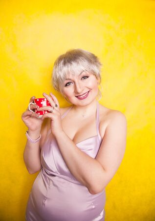 pretty curvy young blonde woman with short hair enjoys drinking tea from cute red polka dot ceramic cup on yellow studio background