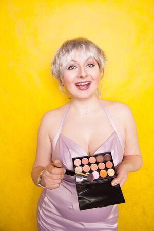 Happy plus size woman having fun with make-up palette set and brush. Professional multicolor eyeshadow face corrector palette.