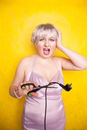 stupid person cuts electric wire with scissors. silly blonde in pink dress plays bad with electricity on yellow studio background