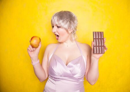 sweet joyous curvaceous girl with a short haircut stands in a delicate evening silk dress and compares bad and good food, deciding what health she wants for herself Stok Fotoğraf