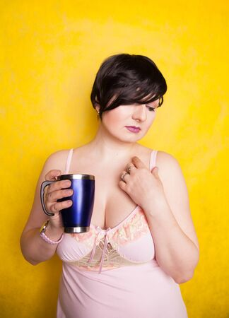 charming girl with a blue thermo mug on a yellow background in the Studio