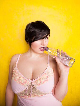 Bella mujer va a beber un poco de agua de una botella de plástico sobre fondo amarillo solo en el estudio Foto de archivo