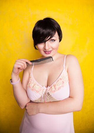 Brunette with Short Hair standing with comb on yellow background alone