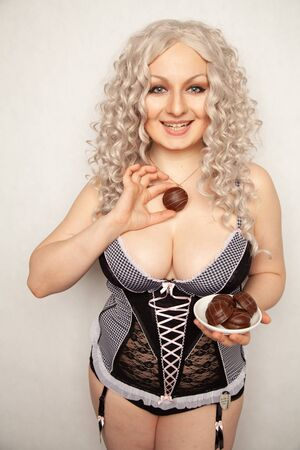 portrait of beautiful plus size curly young blond woman posing on white with marshmallow in chocolate