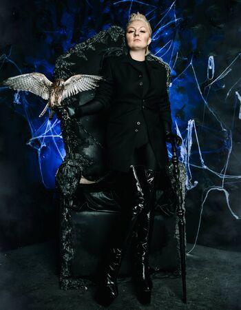 Foto de una reina bruja femenina sosteniendo un pájaro y sentada en un trono negro aterrador gótico Foto de archivo