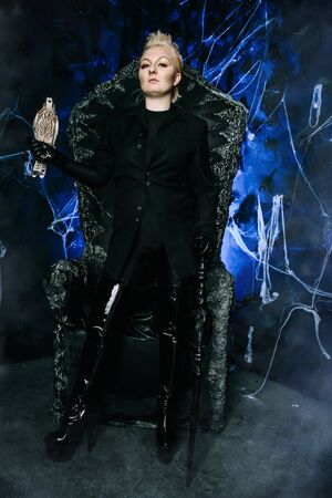 Photo of a female witch queen holding bird and sitting on a gothic scary black throne