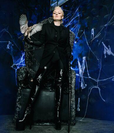 Foto einer weiblichen Hexenkönigin, die einen Vogel hält und auf einem gotischen gruseligen schwarzen Thron sitzt Standard-Bild