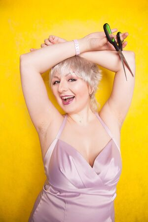 Young happy woman shows unshaving armpit and holds scissors. plus size adult girl with short haircut wants to be natural and does not shave armpits. Фото со стока