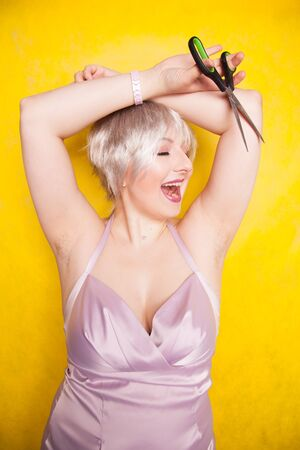 Young happy woman shows unshaving armpit and holds scissors. plus size adult girl with short haircut wants to be natural and does not shave armpits.