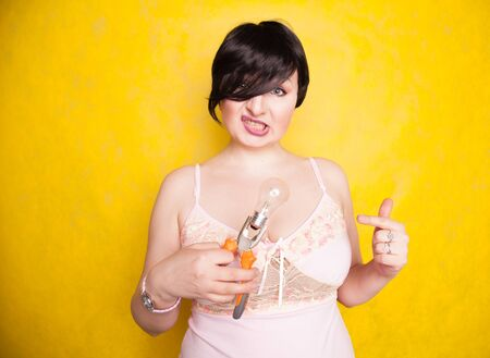 cute funny girl in lingerie stands with pliers and a light bulb and does not know what to do with them, how to make repairs 版權商用圖片 - 131711700