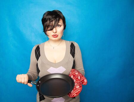 girl with short hair stands in a sweater with a big red kitchen glove and an empty frying pan, ready to cook