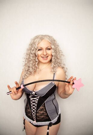 Beautiful blonde dominant mistress girl in fashion cute corset with bdsm black leather riding crop standing and posing on white backgroung in the studio Фото со стока
