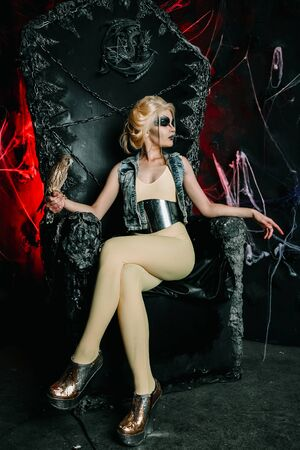 Fashionable halloween model with bird sitting on the big black throne alone in the scary night 写真素材