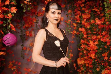 Chica de halloween de moda delgada con cabello negro en vestido de encaje gótico pin up posando en el fondo de otoño con hojas de otoño Foto de archivo