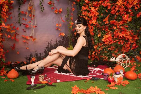 Slim fashion halloween girl with black hair in lace gothic pin up dress posing in the autumn background with fall leaves Stock Photo