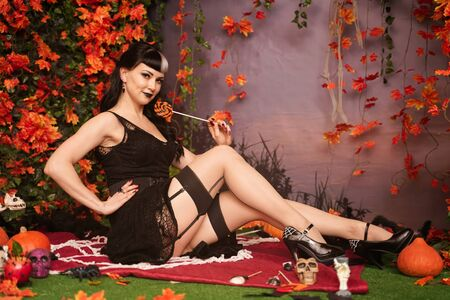 Slim fashion halloween girl with black hair in lace gothic pin up dress posing in the autumn background with fall leaves 版權商用圖片