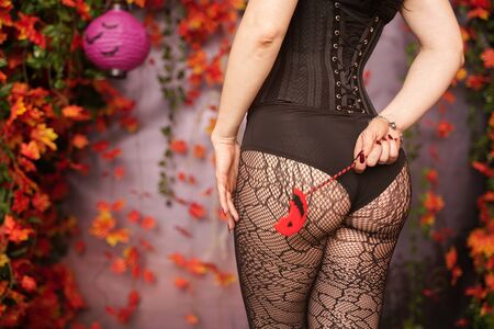 Back of alluring brunette dressed up in black corset and lace pantyhose holding an orange halloween lollipop candy