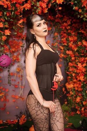 Halloween Vampire Woman portrait. Beautiful Glamour Fashion Sexy Vampire Lady with long black hair with beauty make up and costume