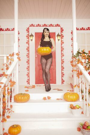 Hot sexy woman come for trick or treat halloween night. Gothic vampire girl on white porch of decorated autumn house.