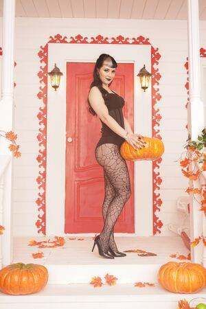 Hot woman come for trick or treat halloween night. Gothic vampire girl on white porch of decorated autumn house.