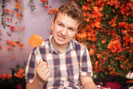 angry disgruntled teenager in plaid shirt sits with pumpkin Lollipop and shows an evil face against the background of autumn leaves. the child is dissatisfied with the result of trick or treat
