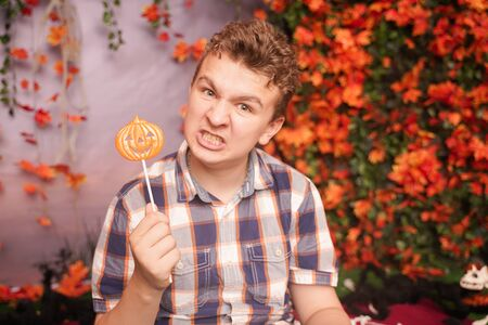 angry disgruntled teenager in plaid shirt sits with pumpkin Lollipop and shows an evil face against the background of autumn leaves. the child is dissatisfied with the result of trick or treat Banque d'images - 131703203