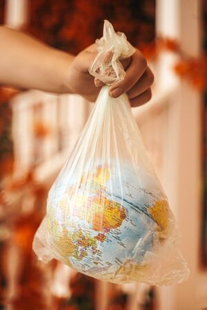 Trapped Planet Earth and an Hand on street Background. the earth suffers and suffocates from plastic Stock fotó