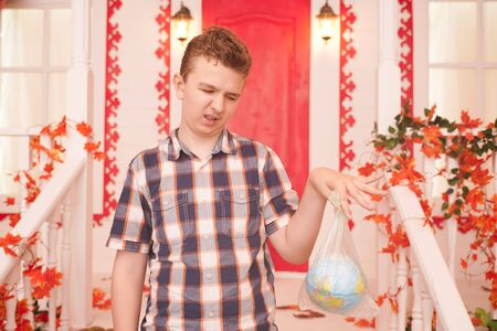 horizontal photo of an emotional teenager holding a planet in a bag and thinking about how his generation will live. concept of planet earth suffering and suffocating from plastic and overheating.