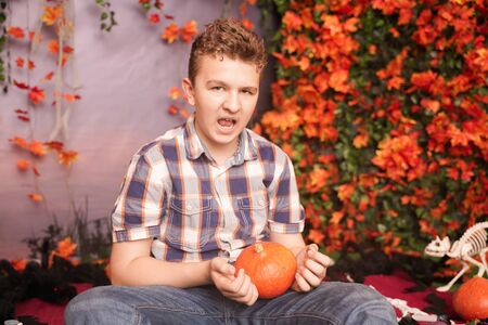 Photo of angry young man on halloween wearing classical plaid shirt holding orange pumpkin over street background with autumn leaves 写真素材