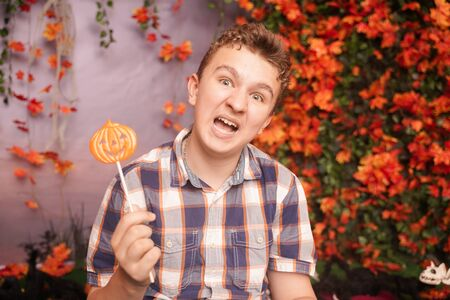angry disgruntled teenager in plaid shirt sits with pumpkin Lollipop and shows an evil face against the background of autumn leaves. the child is dissatisfied with the result of trick or treat Banque d'images - 131720458