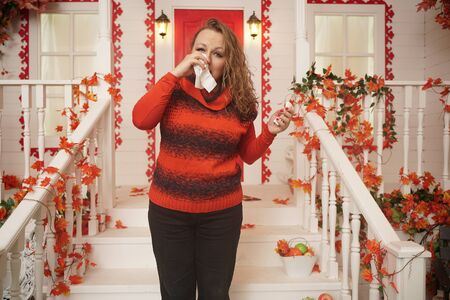 sick plus size woman stands on the porch of her house in the fall and sneezes, blows her nose in a disposable handkerchief Stock Photo