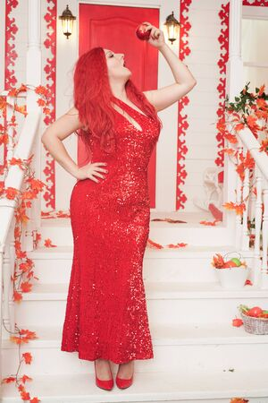 Beautiful autumn chic girl posing with red apple on the porch of white house. gorgeous plus size woman with a curvaceous figure in a long tight full-length evening dress stands and seduces by sin. Banque d'images - 131765448