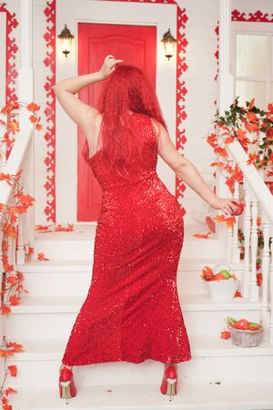Beautiful autumn chic girl posing with red apple on the porch of white house. gorgeous plus size woman with a curvaceous figure in a long tight full-length evening dress stands and seduces by sin. Banque d'images - 131763375