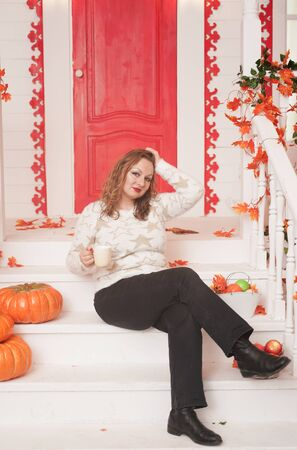Pretty young plus size woman in cozy white sweater drinking the first coffee of the day sitting on the porch of a beautiful autumn house with a red door Standard-Bild