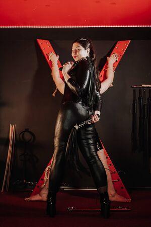 Une femme asiatique sensuelle de grande taille en costume de latex noir joue avec son esclave dans la chambre Banque d'images