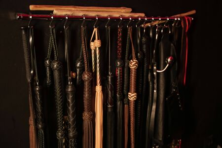 Peitschen für BDSM auf dunklem Hintergrund. Zubehör für Spiele. Standard-Bild