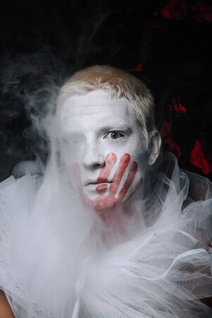 halloween make up. scary man ready for party. guy with face covered in white paint and bloody handprint mark on black studio background with fog Stock Photo
